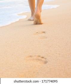 Beach travel. Woman walking on sand beach leaving footprint in the sand.