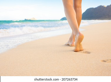 Beach travel - woman walking on beach leaving footprints in the sand. Closeup detail of female feet and golden sand at the beach in Hawaii, USA.