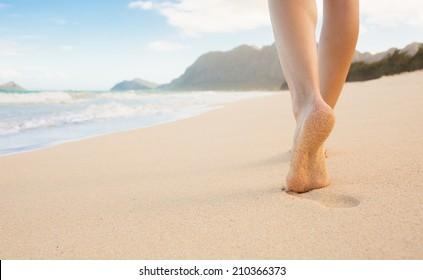 Beach travel - woman walking on sandy beach leaving footprints in the sand.