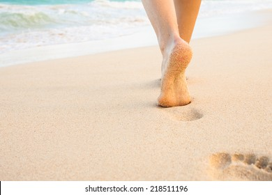Beach travel - woman walking on sandy beach leaving footprints in the sand. Closeup detail of female feet and golden sand on beach in Hawaii