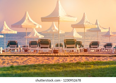 Beach in Turkey with green grass in foreground, white sun shade umbrellas sea and sunset sky in background