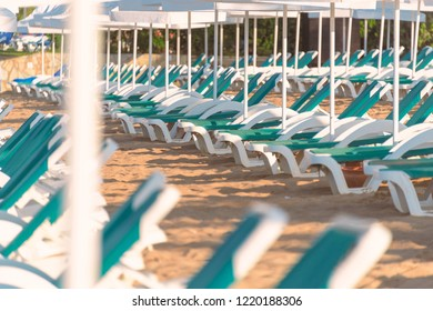 Beach in Turkey with sand in foreground, white sun shade umbrellas and chairs in background