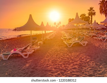 Beach in Turkey with sand in foreground, white sun shade umbrellas and orange sunset sky with sun in background