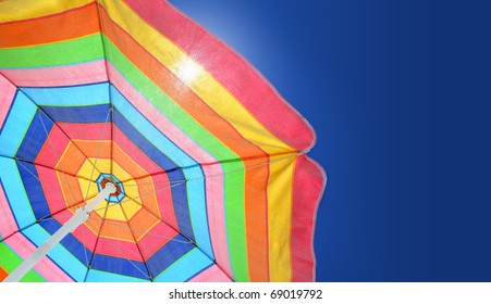 Beach umbrella against sunny blue sky on a summer day. Copy space.