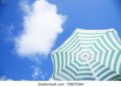 Beach umbrella against sunny blue sky on a summer day.