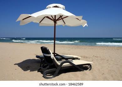 Beach umbrella and beds facing about tides. Bulgaria, Black Sea.