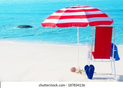 Beach umbrella and chair by the ocean in sunny day