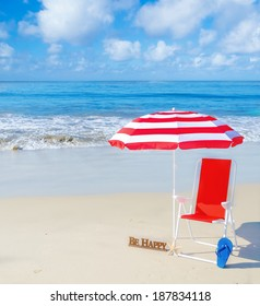 """Beach umbrella, chair and sign """"Be happy"""" by the ocean in sunny day"""