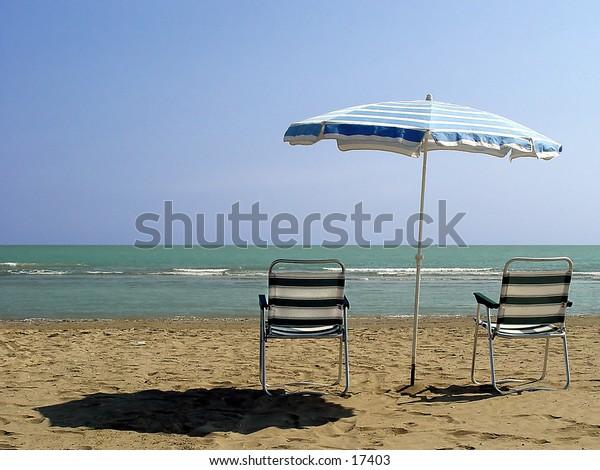Beach umbrella and chairs on a sandy beach