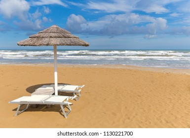 Beach umbrella with chairs on the seaside on a sunny day. Rimini coastline. Italy resort. Copy space on beach background.