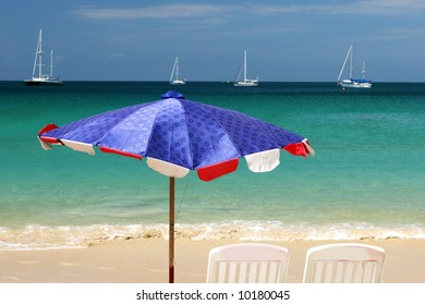 Beach umbrella and chairs overlooking the ocean on a summer day.