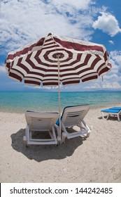 Beach umbrella and deck chairs on the beach. Chalkidiki, Greece  - Shutterstock ID 144242485