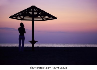 Beach umbrella and the girl silhouette on sunset