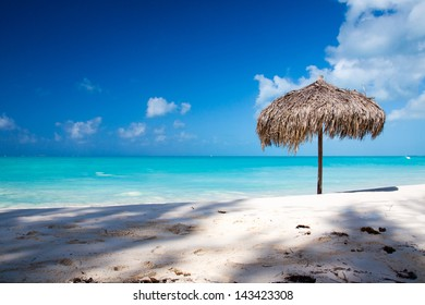 Beach Umbrella made of palm leafs on a perfect white beach in front of Sea. The right place for relax and vacations