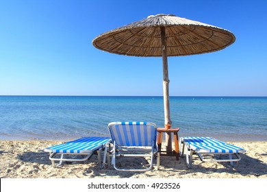 beach umbrella and three chairs in Greece