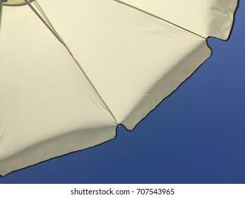 A beach umbrella under a bright summer blue sky.