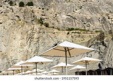 Beach umbrellas and cabins against the backdrop of a high cliff with growing trees