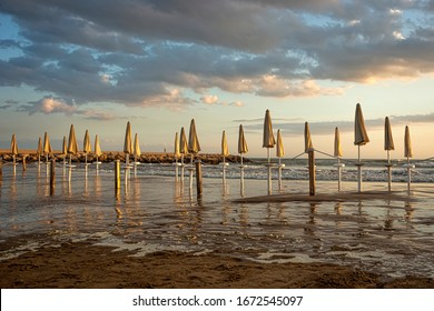 Beach umbrellas closed at sunset. beach of Donnalucata, Sicily