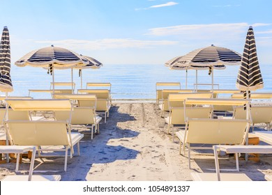 Beach umbrellas and couches on blue sky and sea background on the beach of Italy. Popular Tourist Resort at Adriatic Sea on beach of Milano Marittima, Adriatic coast, Italy