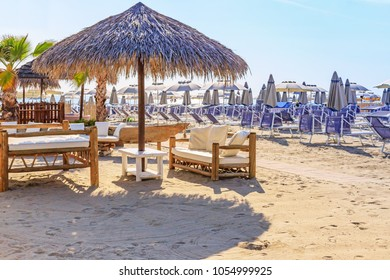 Beach umbrellas and couches on blue sky and sea background on the beach of Italy. Straw and wooden sun umbrellas and chairs.  African style wooden beach furniture on beach of Milano Marittima, Adria