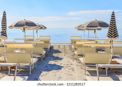 Beach umbrellas and couches on blue sky and sea background on the beach of Italy. Popular Tourist Resort at Adriatic Sea on beach of Milano Marittima, Adriatic coast, Italy.