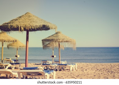 Beach umbrellas and couches on blue sky outdoors background