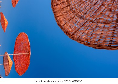 beach umbrellas made of straw at blue sky background, summer photo.