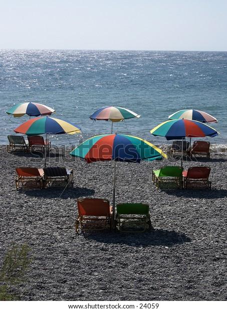 Beach umbrellas on the dark volcanic sand of Thira, Santorini.