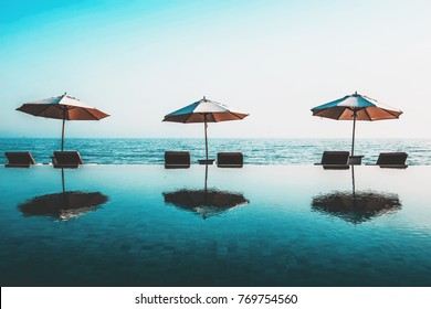 Beach umbrellas and recliner chairs on the rim of an infinity pool at a tropical resort overlooking the calm ocean on a hot summer day in a tourism and vacation concept