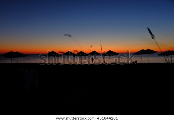 Beach umbrellas silhouettes in front of evening sky and steams of fluttering grass on foreground blurred