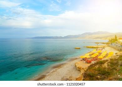 Beach with umbrellas sunbeds on coast of Crete, with people resting. Hersonissos, Crete.