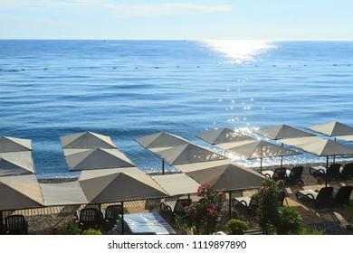 Beach umbrellas with sunbeds on the Mediterranean Sea in Kemer, Turkey