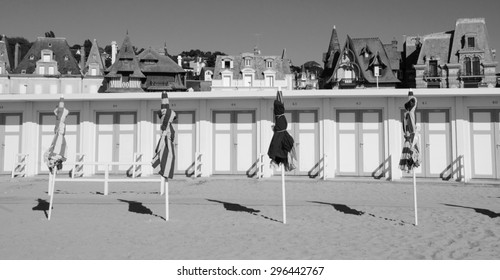 Beach umbrellas and wooden cabins at the beach of Trouville-sur-Mer (Normandy, France). Aged photo. Black and white.