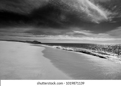 Beach under cirrus cloudscape at the Todos Santos artist community in central Baja California Mexico BCS - black and white