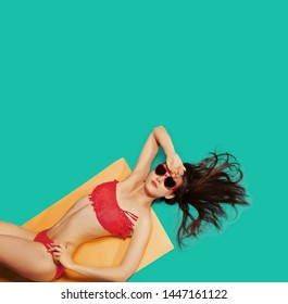 Beach Vacation abstract concept. Colorful studio portrait of young Fashion Woman in red swimsuit and sunglasses. Isolated on Blue background like sea water