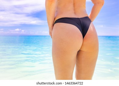 Beach vacation banner. Sexy woman buttocks on tropical beach background blurred ocean. Closeup outdoor shot of young woman in black bikini, sunbathing at sea shore. Black bikini on ocean background