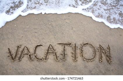 Beach Vacation concept written in sand as ocean waves approach.
