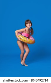 Beach Vacation concept.Happy cute little girl smiling holding swimming ring on body.Pretty fashion child dressed in swimsuit fun poses.Beautifu kid teenager loves summertime.Isolated blue background.