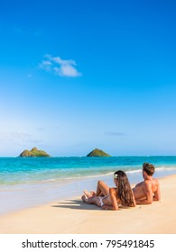 Beach vacation couple relaxing sunbathing on hawaiian tropical beach in Lanikai, Oahu, Hawaii, USA. American people on summer holidays sun tanning lying down on sand.