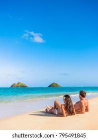 Beach vacation couple relaxing sunbathing on hawaiian tropical beach in Lanikai, Oahu, Hawaii, USA. American people on summer holidays sun tanning lying down on sand.