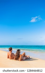 Beach vacation couple tanning under the tropical sun enjoying summer holidays traveling aroung the world. Young people lying down in paradise. Vertical background with copy space on sky.