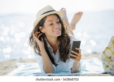Beach vacation girl using mobile phone app texting sms or sharing photos on social media