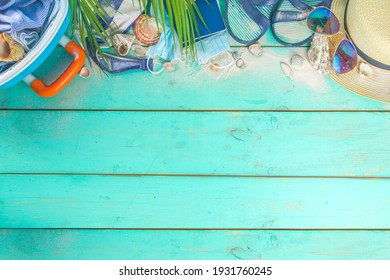 Beach and Vacation Holiday Accessories On Blue Plank. Suitcase for travel, summer women's clothing, sunglasses, accessories and tropical leaves on bright blue background copy space for text top view
