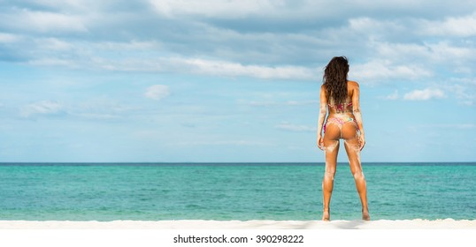 Beach vacation. Hot beautiful woman in bikini standing and  enjoying looking view of beach ocean on hot summer day. Banner