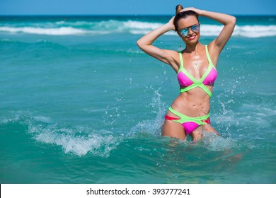 Beach vacation. Hot beautiful woman in sunglasses and bikini standing with her arms raised to her head enjoying looking view of beach ocean on hot summer day.