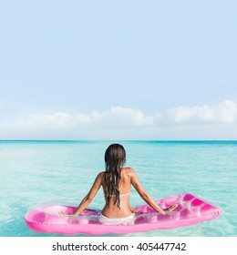 Beach vacation relaxation on ocean water bed. Bikini woman from the back sitting on a pink pool floating air mattress looking at horizon of the perfect turquoise pristine sea in tropical destination.