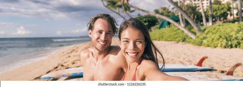 Beach vacation selfie couple. Happy young interracial friends taking photo with phone after surfing class on tropical Hawaii beach. Banner panorama. Travel vacation destination watersports.