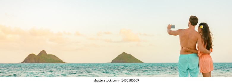 Beach vacation tourists couple taking picture with phone of Hawaii islands on ocean banner panoramic background. Honeymoon summer travel holidays.