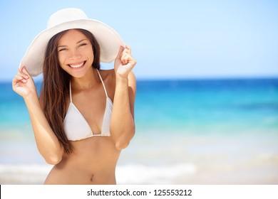 Beach vacation woman in sun smiling happy on summer holidays on tropical beach. Beautiful multiethnic asian chinese / caucasian bikini model wearing beach hat.