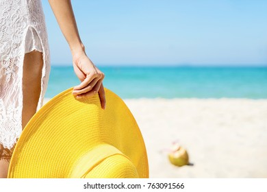 Beach vacation. woman with sunhat standing with her arm hold her yellow straw hat view of beach ocean on hot summer day.